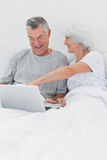 Mature woman pointing at husbands laptop Royalty Free Stock Image