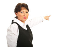 Mature woman pointing to background Stock Images