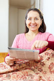 Mature woman pointing to newspaper Stock Photo