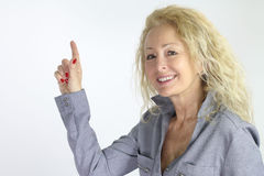 Mature woman pointing a white background Stock Images