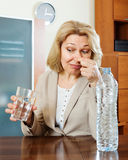 Mature woman with poor quality water. Sad mature woman with grass of poor quality water stock images