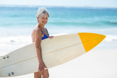 Mature woman posing with a surfboard Royalty Free Stock Photo