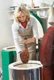 Mature Woman In Pottery Studio Firing Vase In Kiln. Woman In Pottery Studio Firing Vase In Kiln stock photo
