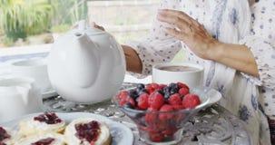 Mature woman pouring lemon tea into cup 4k stock video