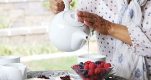 Mature woman pouring lemon tea into cup 4k stock footage