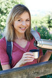 Mature Woman Pouring Hot Drink From Flask On Walk stock images