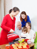 Mature woman pours tea  for three generations family Royalty Free Stock Images