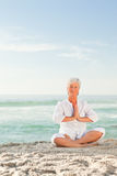 Mature woman practicing yoga on the beach stock photos