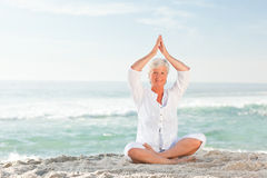 Mature woman practicing yoga on the beach Royalty Free Stock Photos