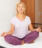 Mature woman practicing yoga Stock Image