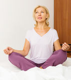 Mature woman practicing yoga Stock Images