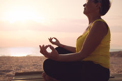 Mature woman practicing yoga. At lotus pose, at the sea beach Stock Photos