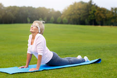 Mature woman practicing yoga in the park stock photography