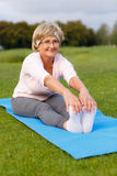 Mature woman practicing yoga in the park. Mature woman practicing yoga in evening in the park Royalty Free Stock Photography