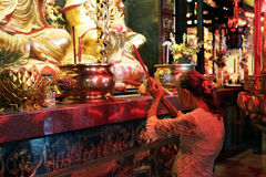 Mature Woman Praying in Buddhist Temple Royalty Free Stock Image