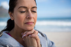 Mature woman praying with hands clasped. On beach Royalty Free Stock Photos