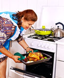 Mature woman preparing chicken at kitchen. Royalty Free Stock Photos