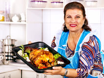 Mature woman preparing chicken at kitchen. Royalty Free Stock Photo
