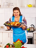 Mature woman preparing chicken at kitchen. Stock Photo