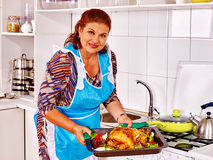 Mature woman preparing chicken at kitchen Stock Photography