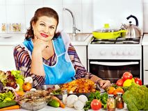 Mature woman preparing at kitchen. Stock Images