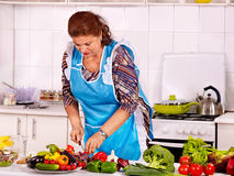 Mature woman preparing at kitchen Stock Photos