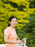 Mature woman preparing to paint outdoor deck railing Royalty Free Stock Images