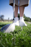 Mature woman preparing to tee off with driver on golf course, close-up, low section (surface level) royalty free stock images