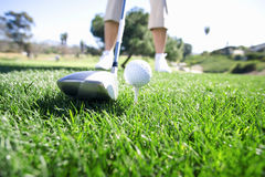 Mature woman preparing to tee off with driver on golf course, low section (surface level) royalty free stock photography