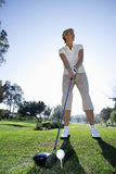 Mature woman preparing to tee off with driver on golf course, smiling (surface level) Stock Photo