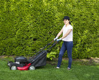 Mature Woman Preparing to work on Grass Yard. Horizontal photo of a mature woman preparing to use an old gas lawnmower on grass yard with tall bushes and flower Royalty Free Stock Image