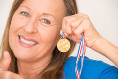 Mature woman presenting medal Royalty Free Stock Photography