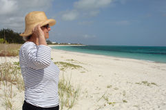 Mature woman in profle looks out at sea stock photography