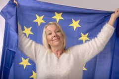 Mature woman proudly holding the European Union flag. Taken on a white background stock photography