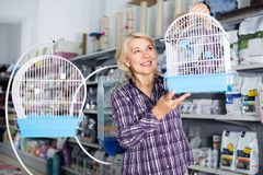 Portrait of mature woman purchasing bird cage in petshop. Mature woman purchasing bird cage in petshop Royalty Free Stock Images