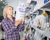 Mature woman purchasing pet food in petshop. Portrait of mature woman purchasing pet food in petshop Stock Photos