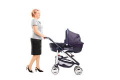 Mature woman pushing a baby stroller Royalty Free Stock Photo