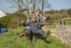 Mature woman pushing senior woman in wheelbarrow. Mature women pushing senior women in wheelbarrow outdoors in spring stock photo