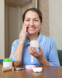 Mature woman puts cream on face Royalty Free Stock Images