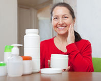 Mature woman puts cream on face Royalty Free Stock Photography