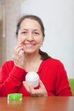 Mature woman  puts cream on face Stock Image