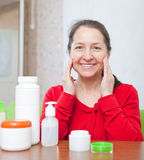Mature woman  puts cream on face at home interior Royalty Free Stock Images