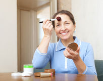 Mature woman puts facepowder on  face Royalty Free Stock Photography