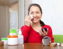 Mature woman puts facepowder on  face Royalty Free Stock Photo