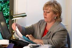 Mature woman puts paper in envelope Stock Images