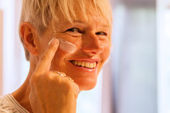 Mature woman puts on some lotion in the face Stock Photography
