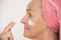 Mature woman putting cream on face Royalty Free Stock Image