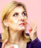 Mature woman putting face cream on Stock Photo