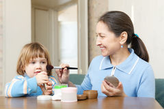 Mature woman  putting facepowder on   little girl Stock Photo