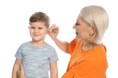Mature woman putting hearing aid in little grandson`s ear royalty free stock image